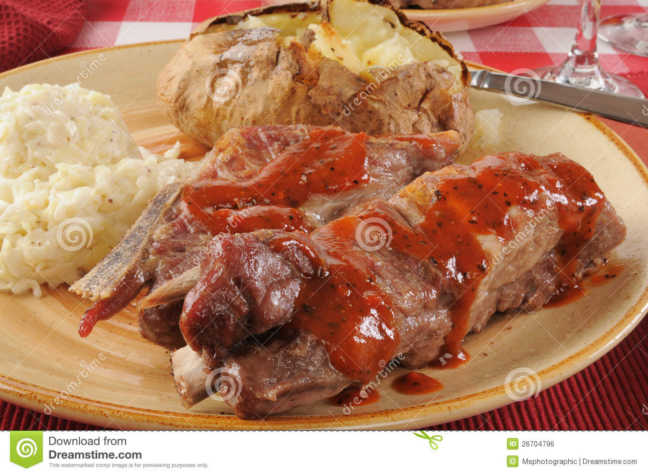 Closeup of barbecued pork ribs with a baked potato and coleslaw.
