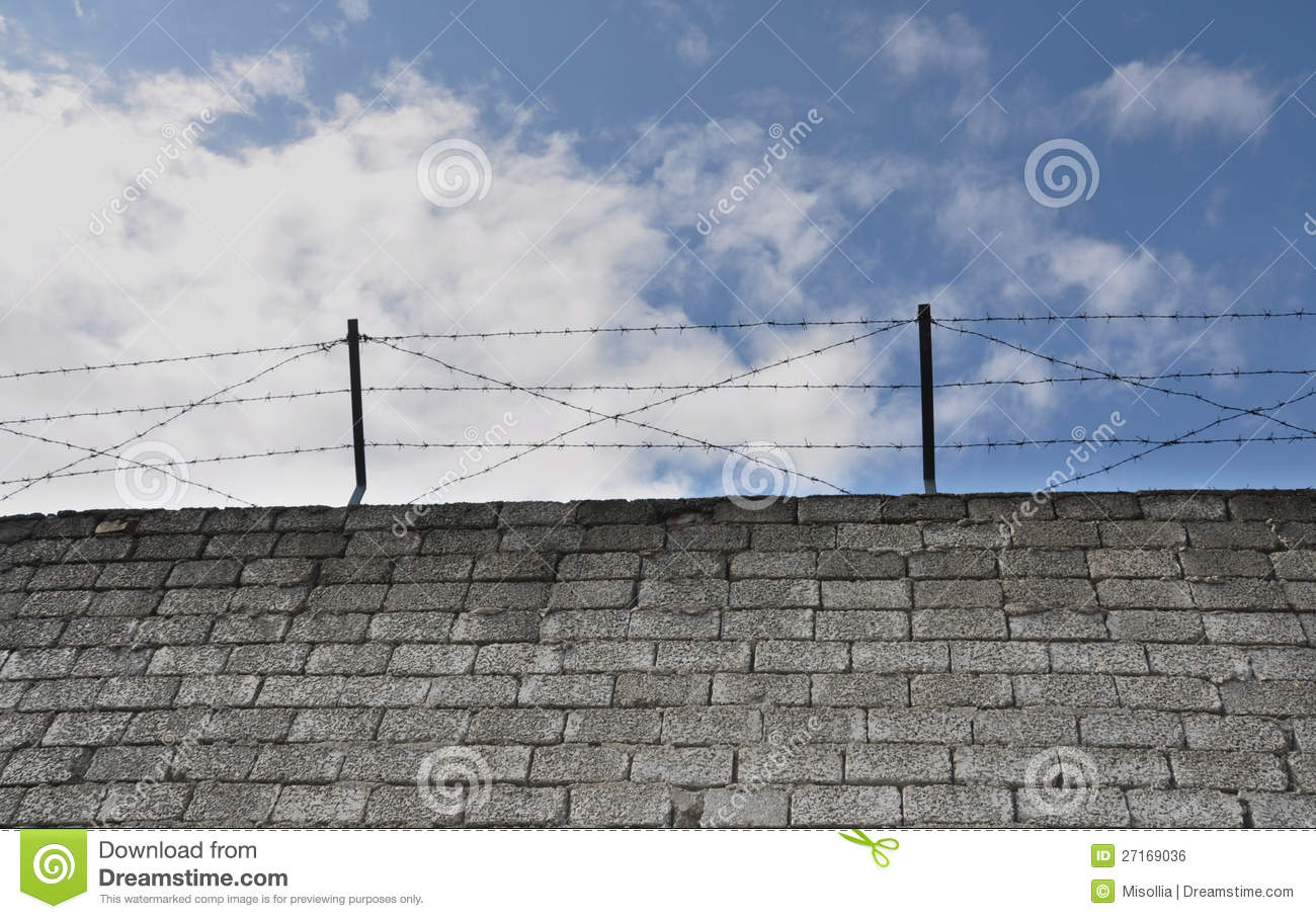 Barbed wire above a stone wall royalty free stock image