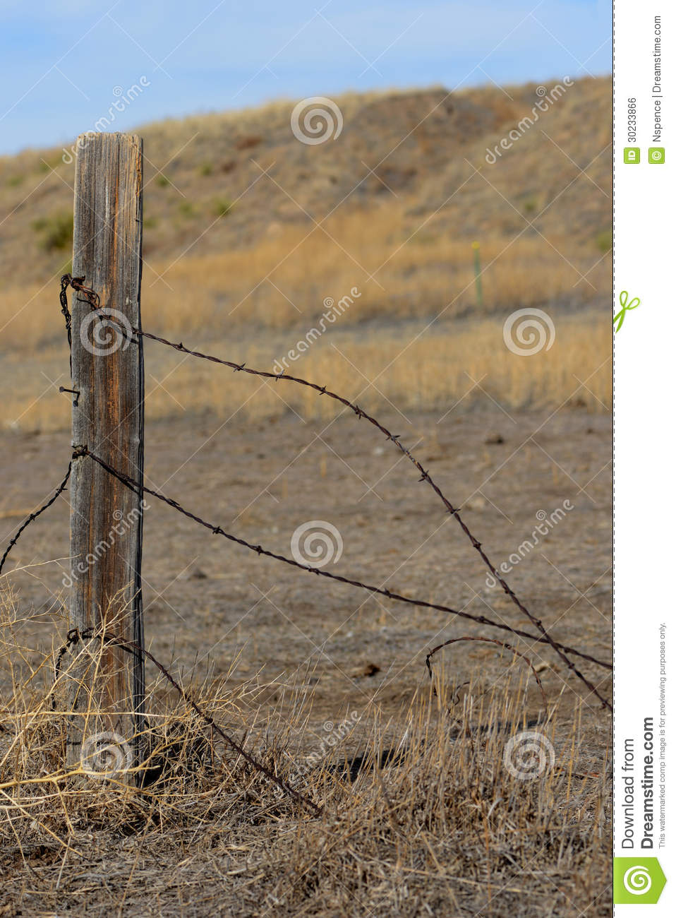 Barbed wire and fence post with wild prairie background