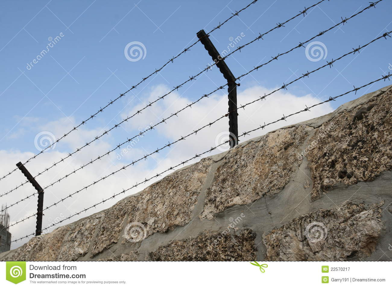 Barbed wire over the stone wall stock image