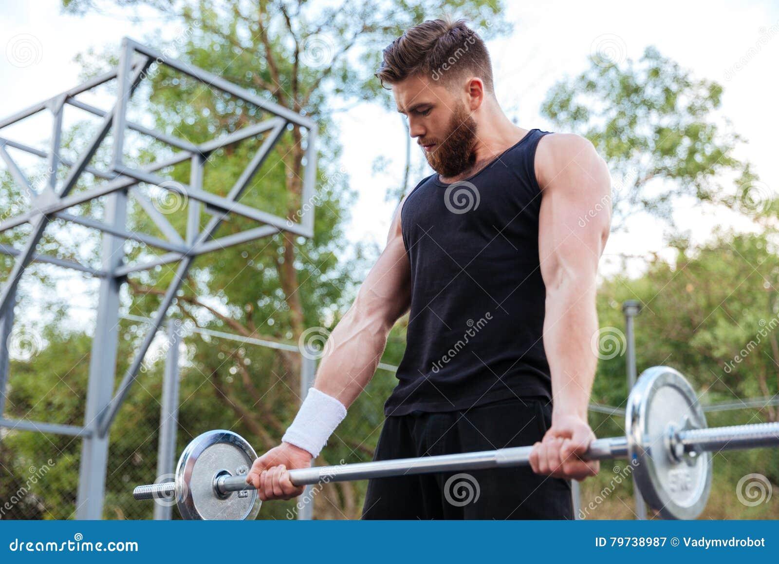Barbell de elevación del hombre barbudo joven serio de la aptitud