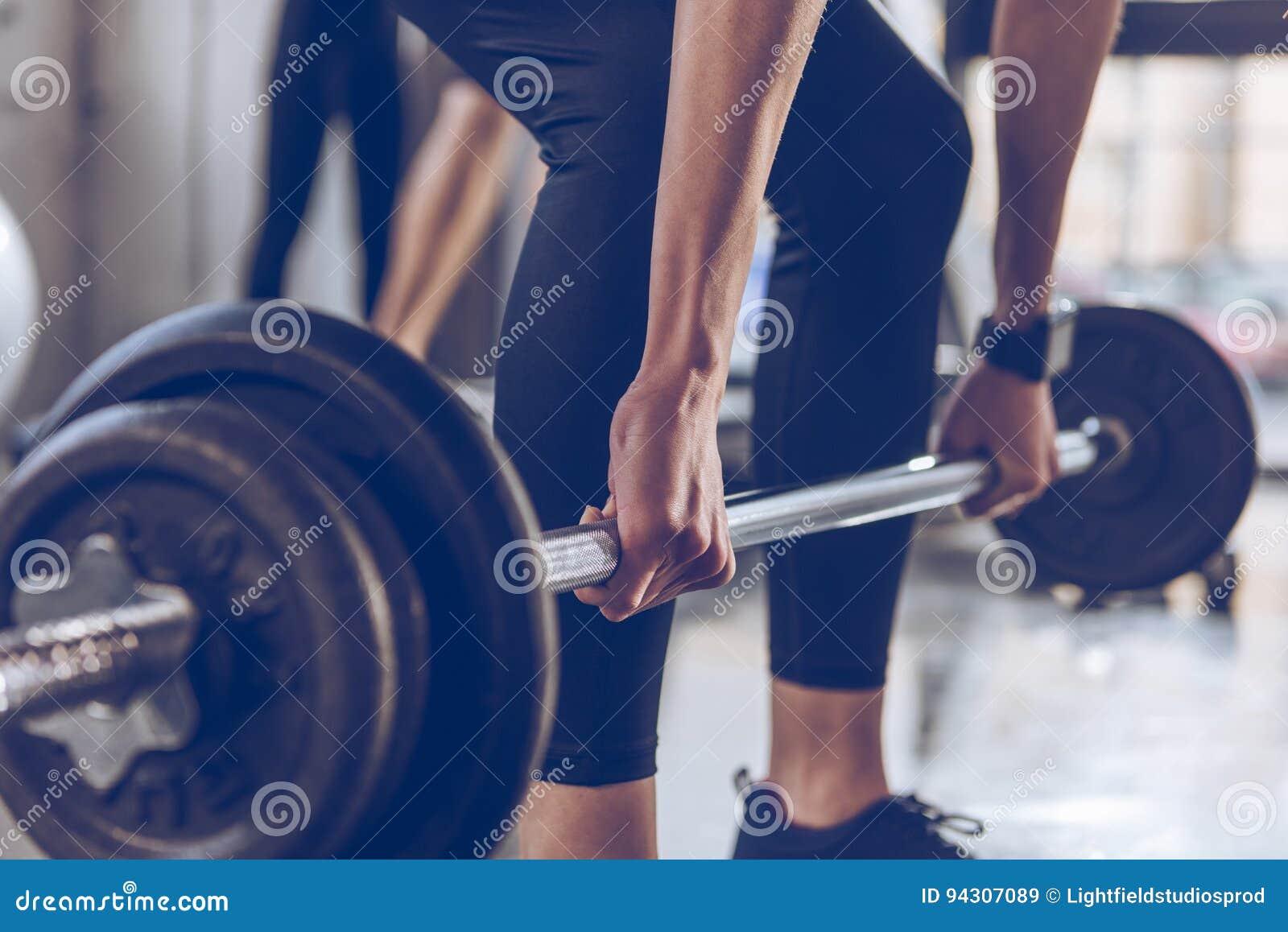Barbell de levage de sportive à la séance d entraînement de gymnase