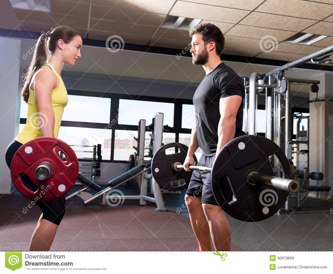Barbell Man And Woman Workout At Fitness Gym