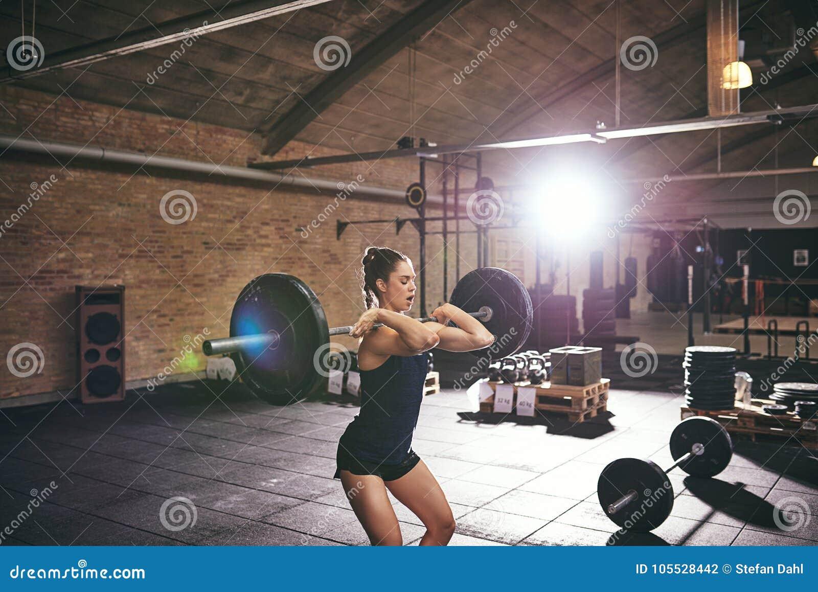 Barbells de levage de jeune femelle musculaire dans le gymnase