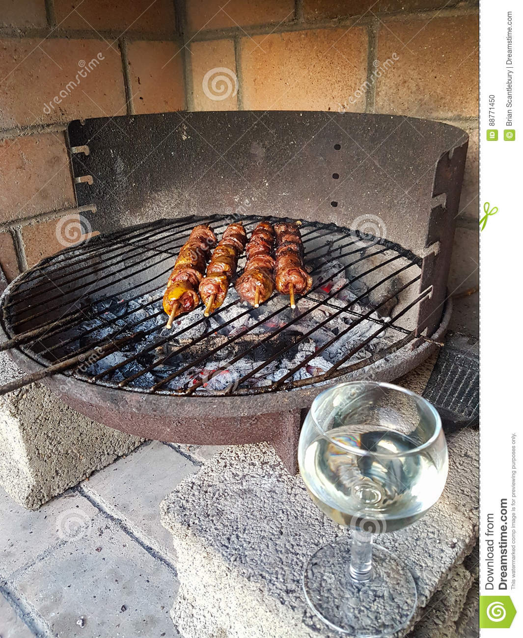 Barbequing kebabs over smoldering charcoal on old fashioned styl stock photo image 88771450