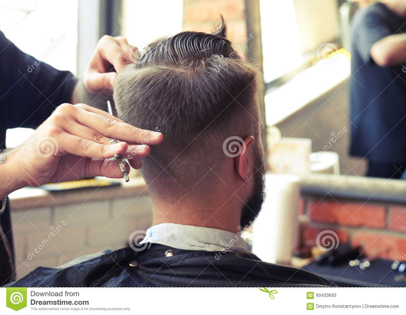 Barber cutting hair with scissors