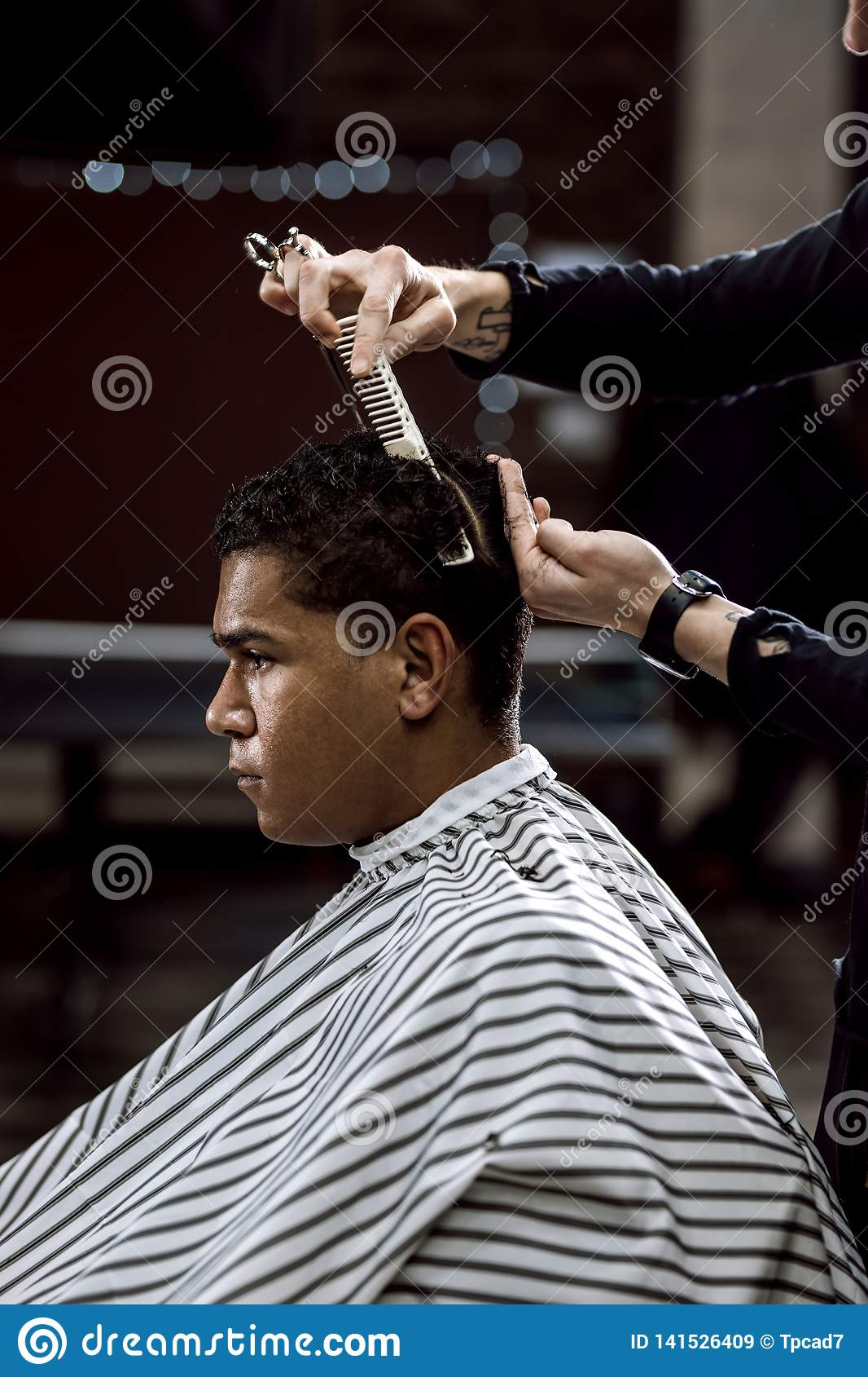 The barber is cutting a man`s hair holding scissors and comb in his hands opposite the mirror in a barbershop