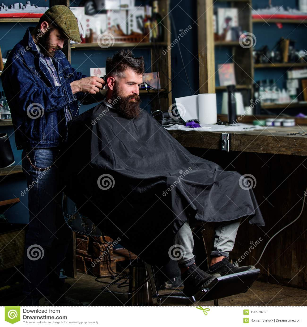 Barber with hair clipper works on haircut of bearded guy barbershop background. Hipster client getting haircut. Barber
