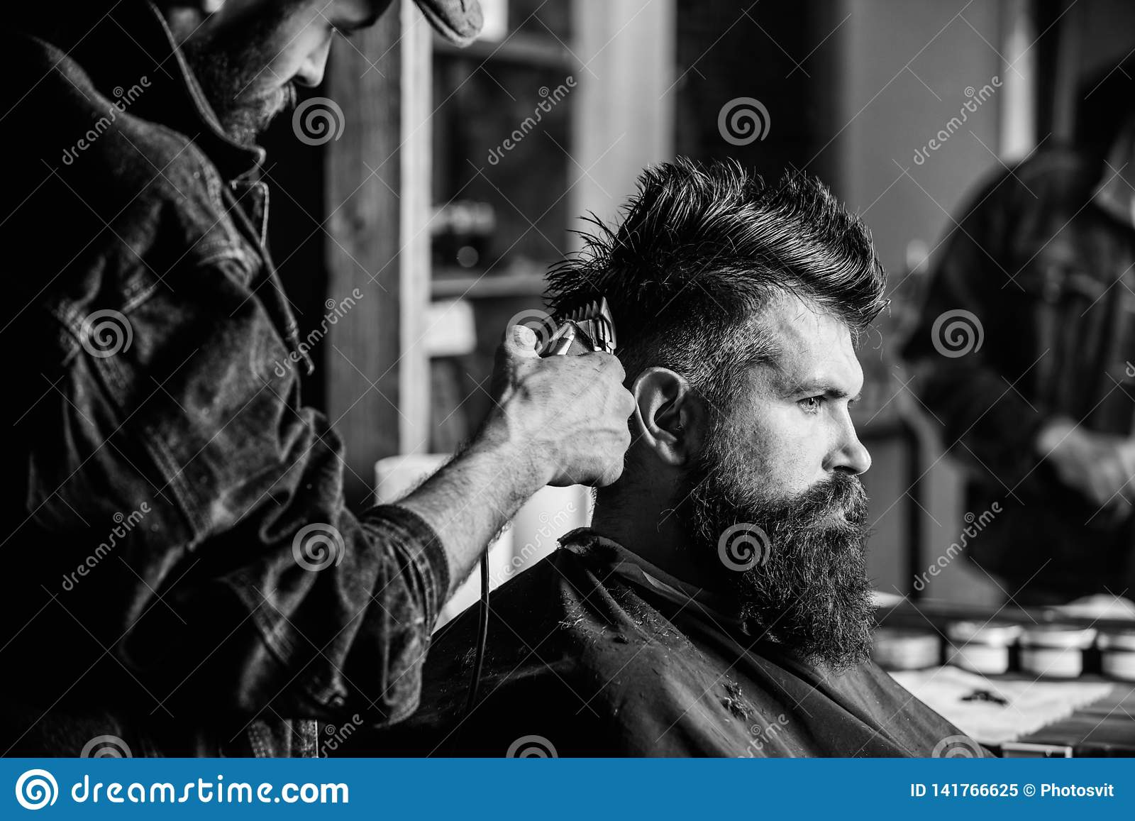 Barber with hair clipper works on hairstyle for bearded man barbershop background. Barber styling hair of brutal bearded