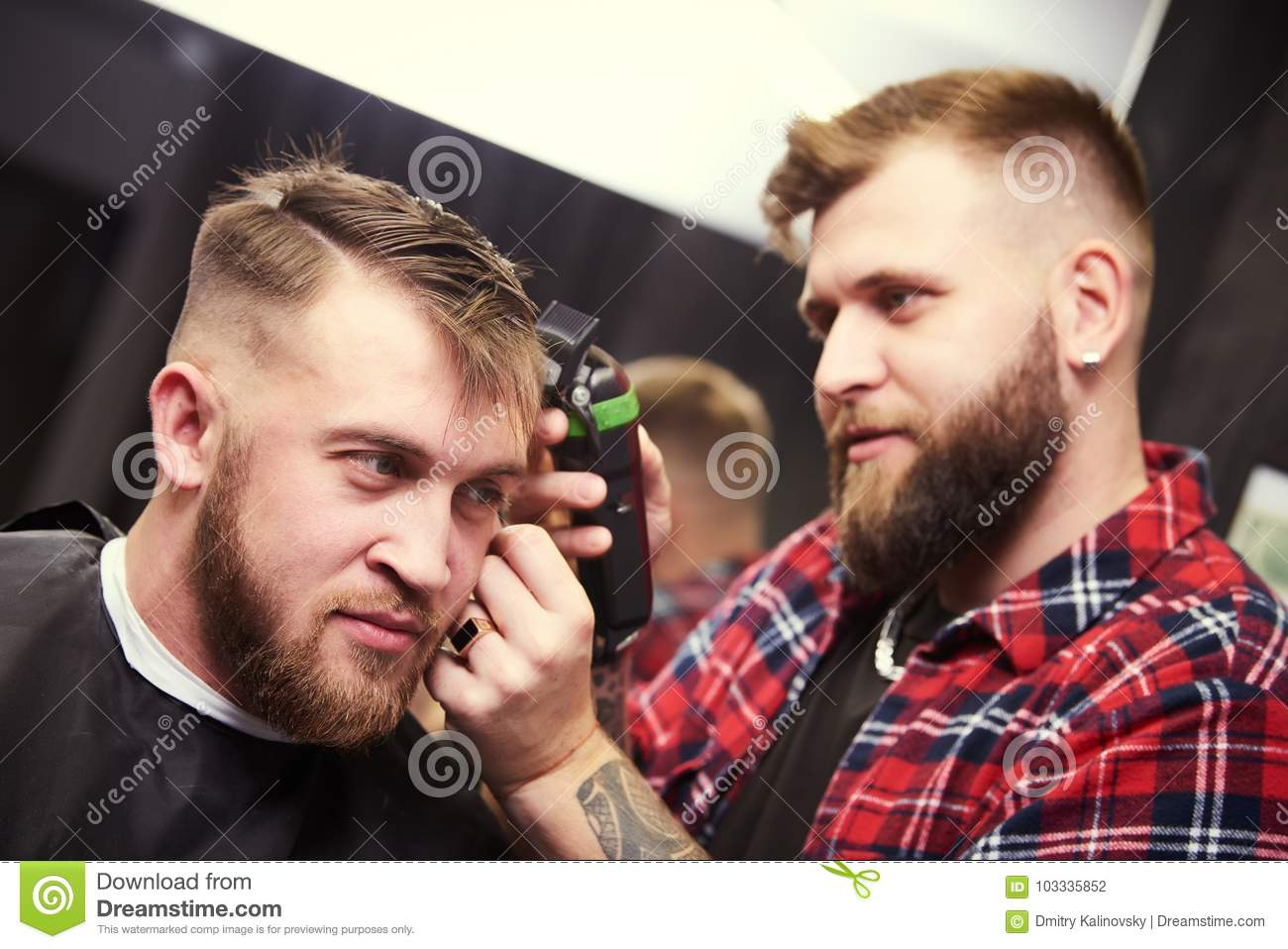 Barber or hair stylist at work. Hairdresser cutting hair of client