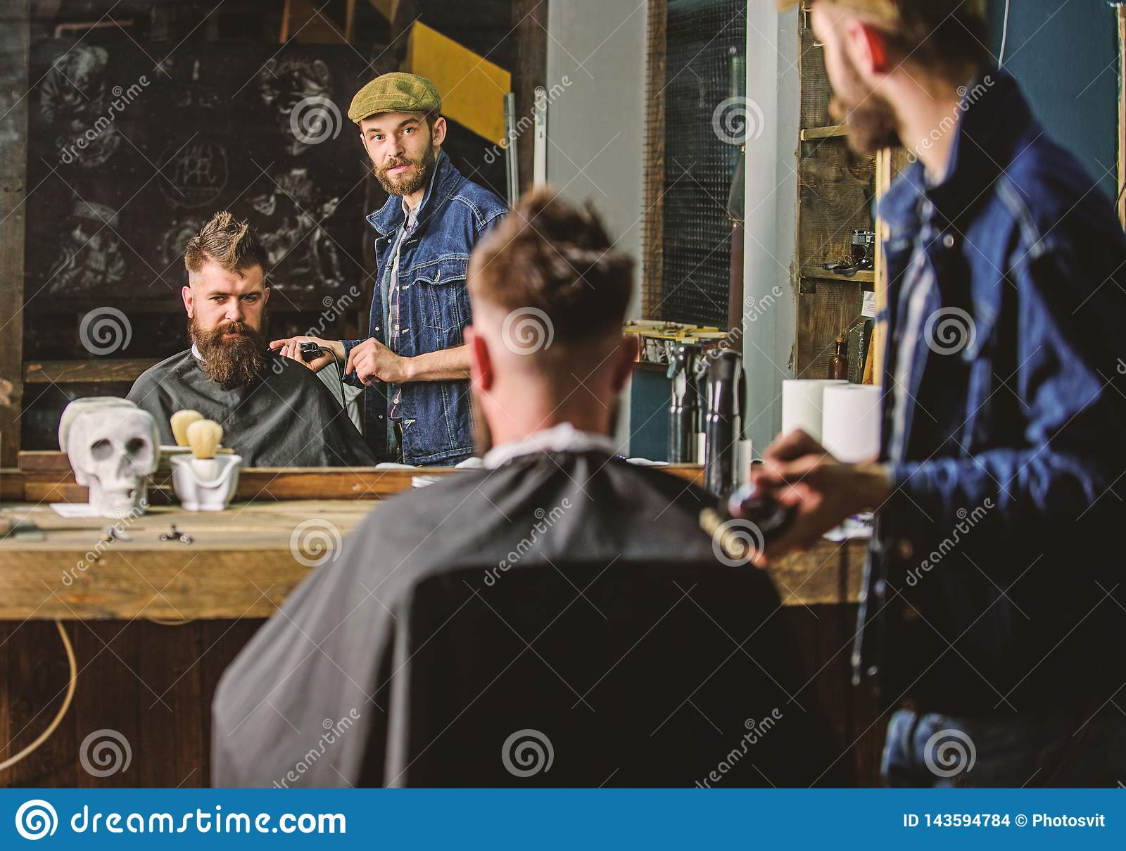 Barber preparing hair clipper for bearded man, barbershop background. Hipster lifestyle concept. Hipster client covered
