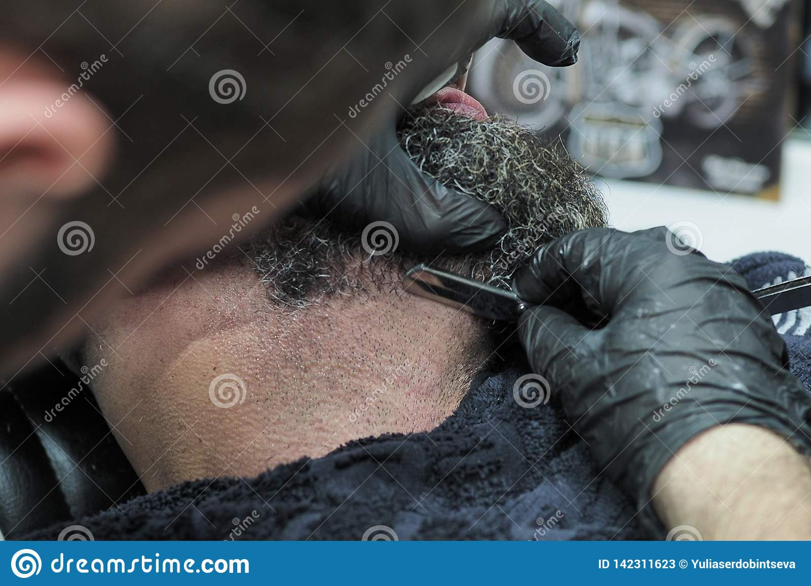 Barber shaves the beard of an elderly man with gray hair sharp razor