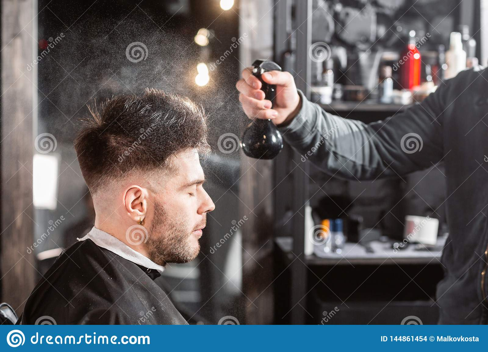 Barber sprays clean water on head in barbershop. Professional trimmer tool cuts beard and hair on young guy in barber