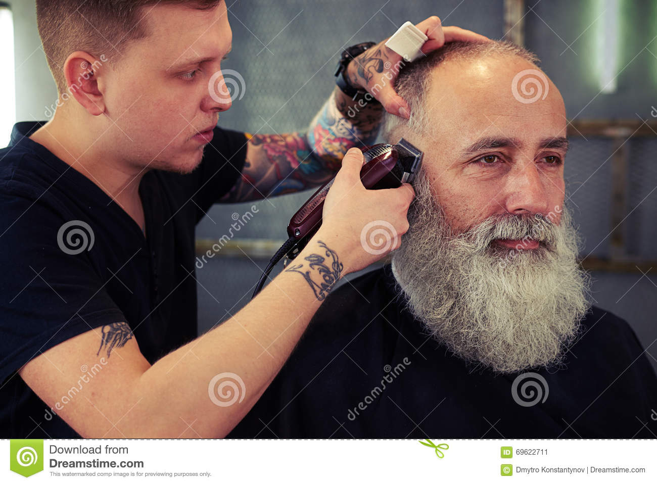 Barber With Tattoo Making Haircut To Handsome Hipster Senior Man