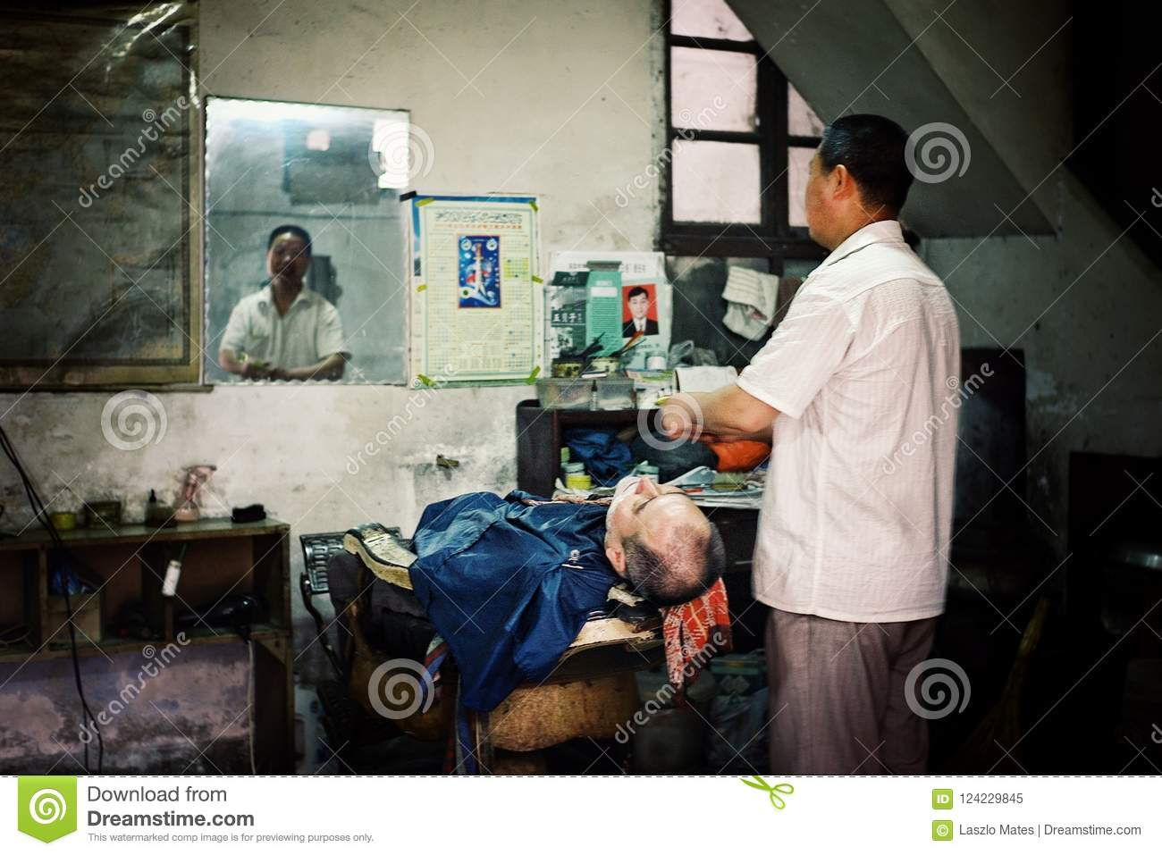 Barber trimming a client at a small traditional chinese barber shop
