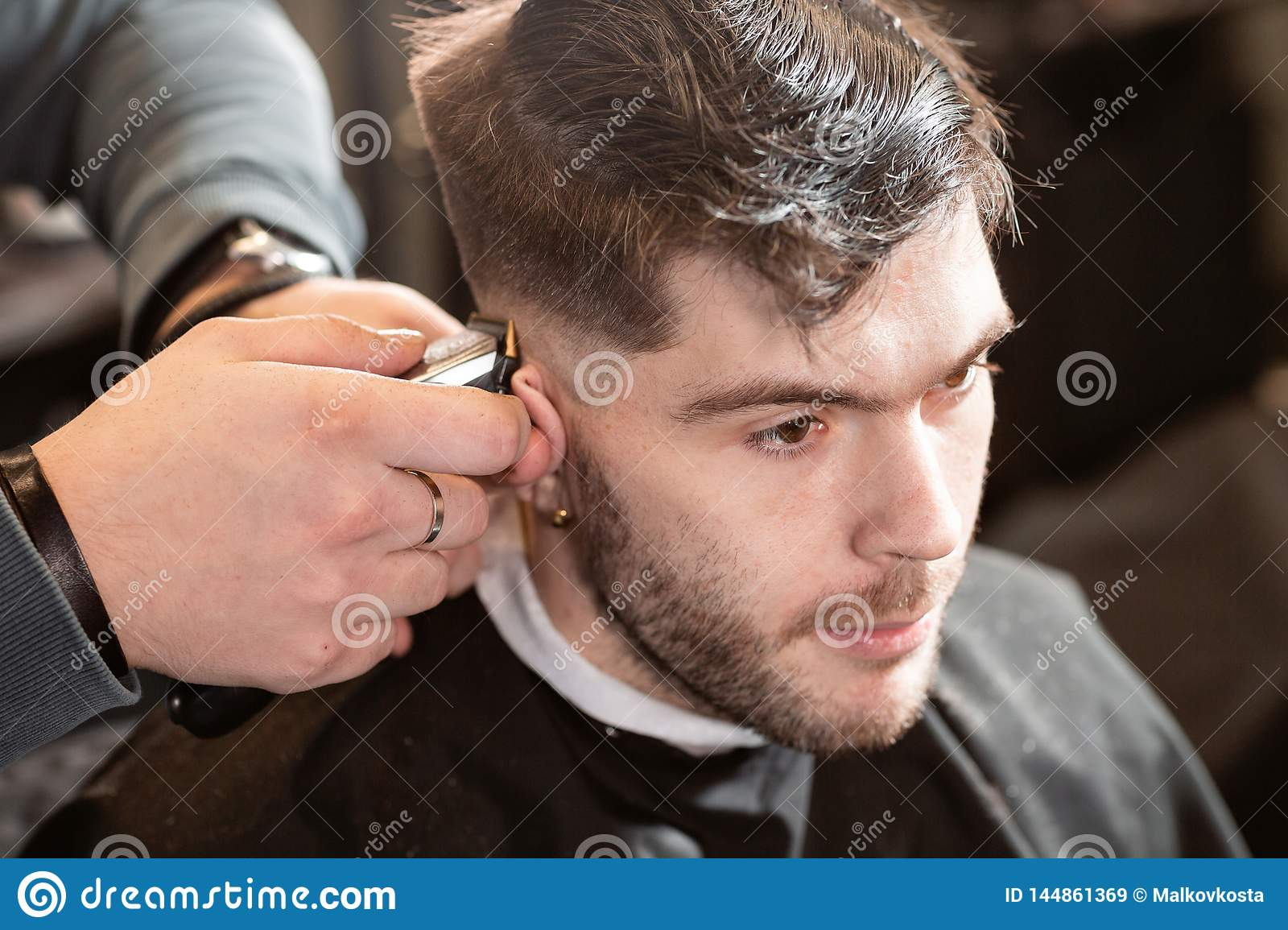 Barber work with clipper machine in barbershop. Professional trimmer tool cuts beard and hair on young guy in barber