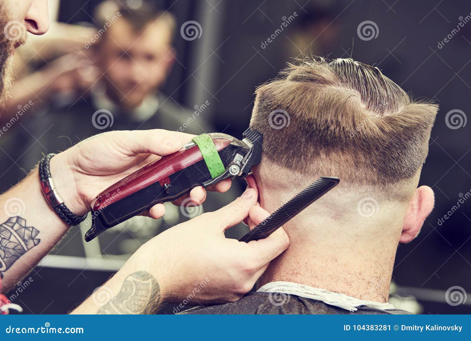 Barberare- eller hårstylist på arbete Bitande hår för frisör av klienten