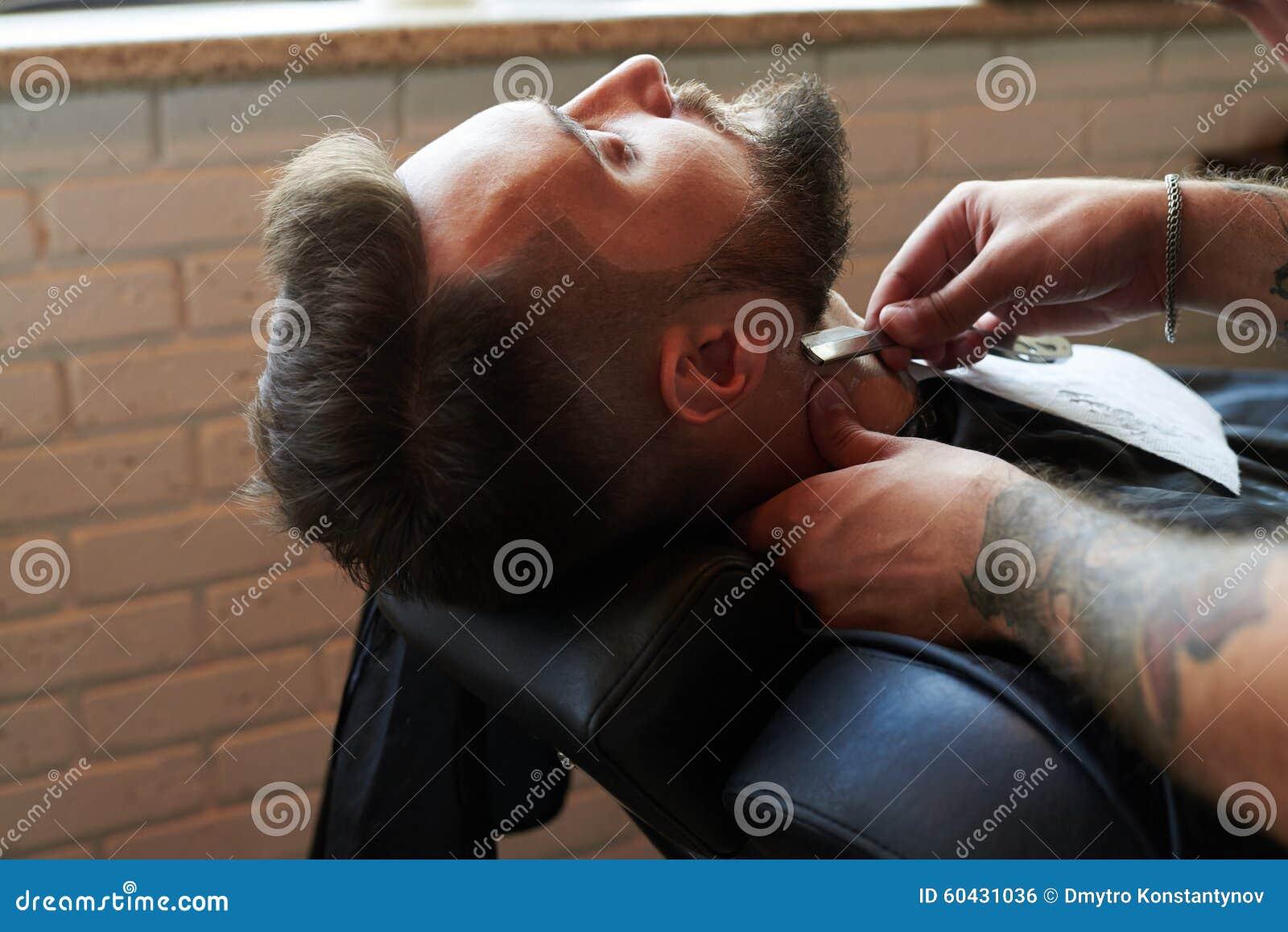 Barberare som rakar med den raka rakkniven för tappning