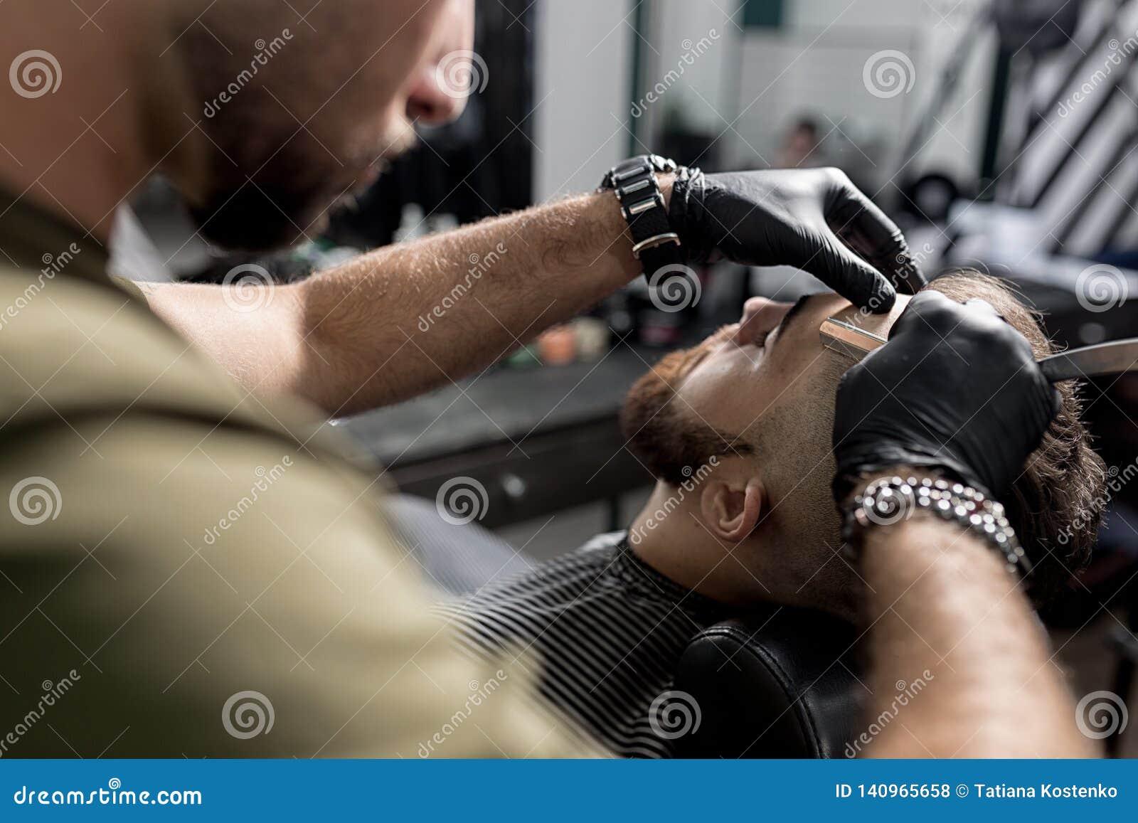 Barberaren i svarta handskar klipper templet av den brutala skäggiga unga mannen med en rak rakkniv på en frisersalong