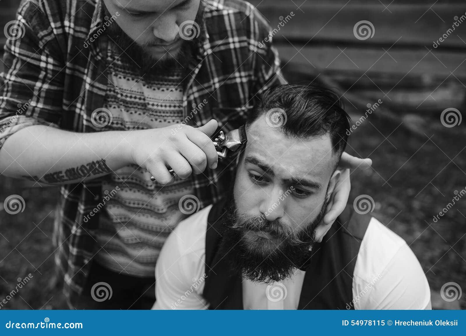 Barberaren rakar en skäggig man utomhus