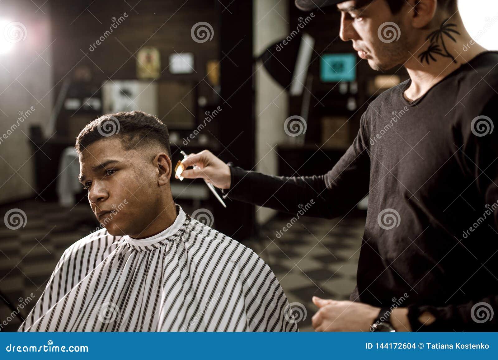 Barberaresaxhåret på sidorna för en stilfull svart-haired man i frisersalongen Mode och stil för man` s