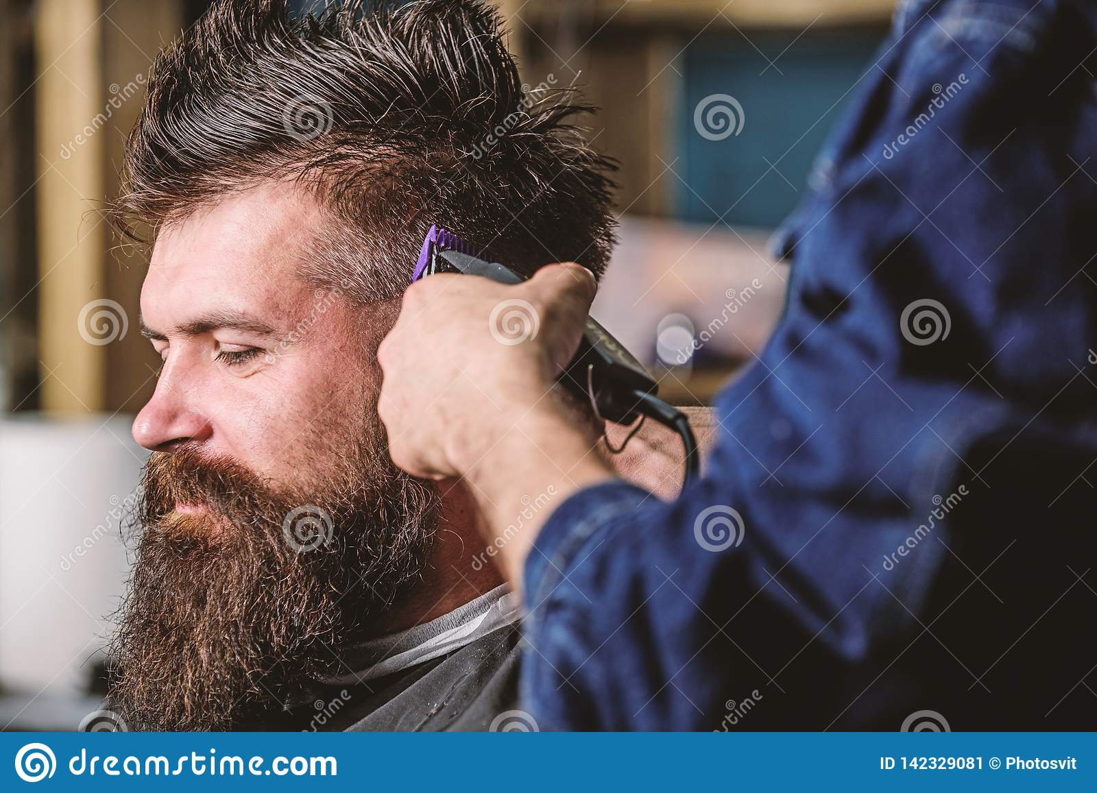 Barbershop concept. Hands of barber with hair clipper, close up. Hipster bearded client getting hairstyle. Barber works