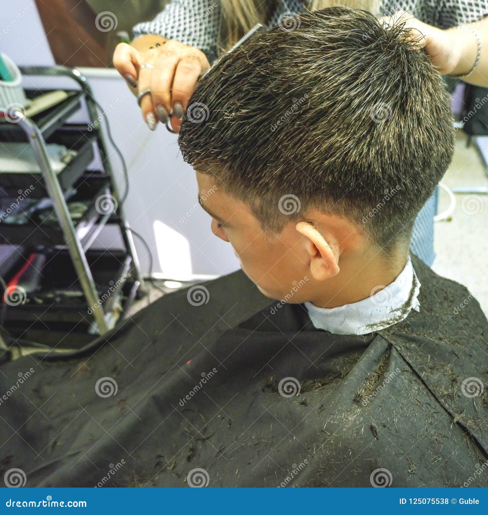 Barbershop Il primo piano dei tagli di capelli adolescente, padrone fa il taglio di capelli dei capelli nel negozio di barbiere