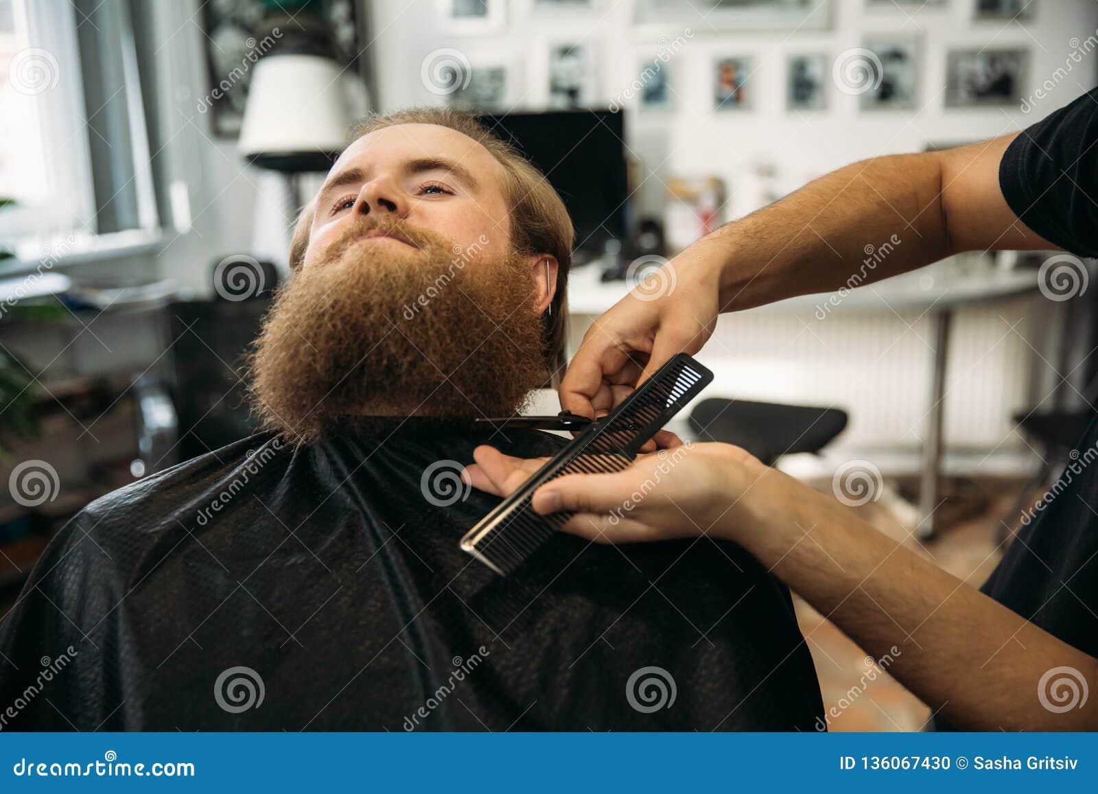 Barbiere che utilizza le forbici e pettine nel parrucchiere
