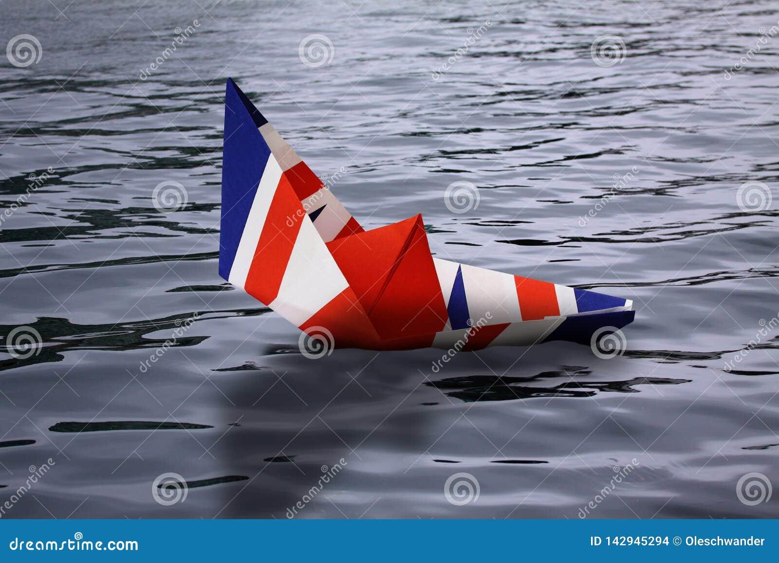 Barca di carta fatta come la bandiera britannica che affonda nella rappresentazione acqua Inghilterra di concetto che lascia Unio