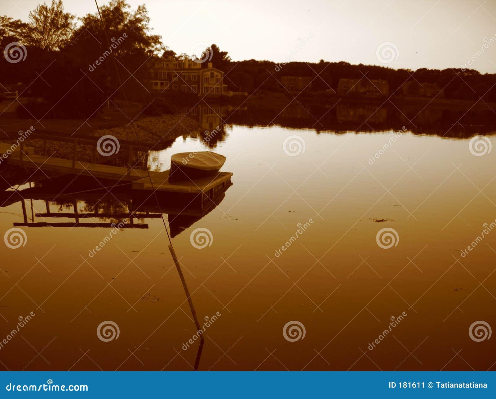 Barca e stagno al tramonto nella seppia