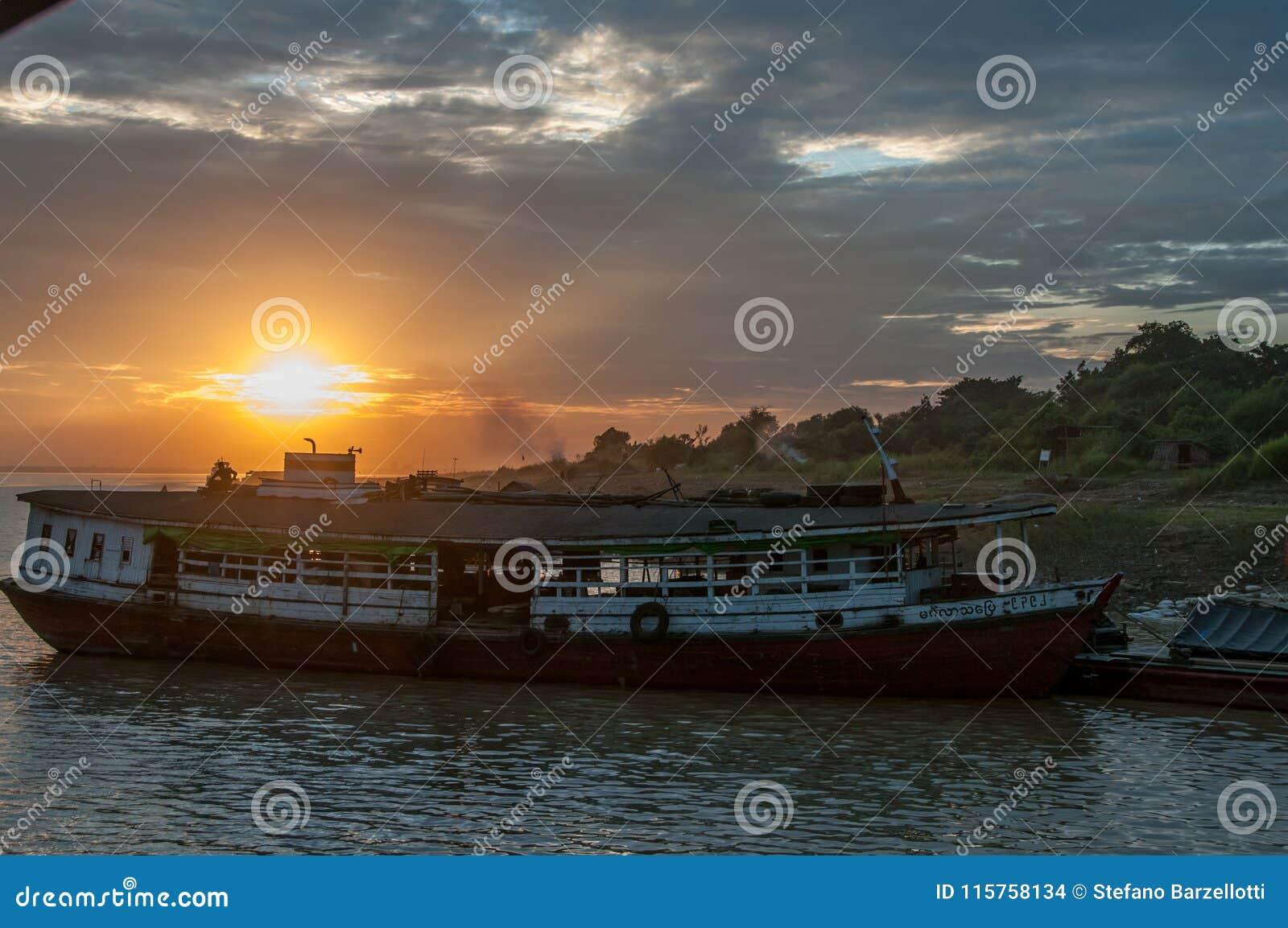 Barca e tramonto sul fiume di Irrawaddy