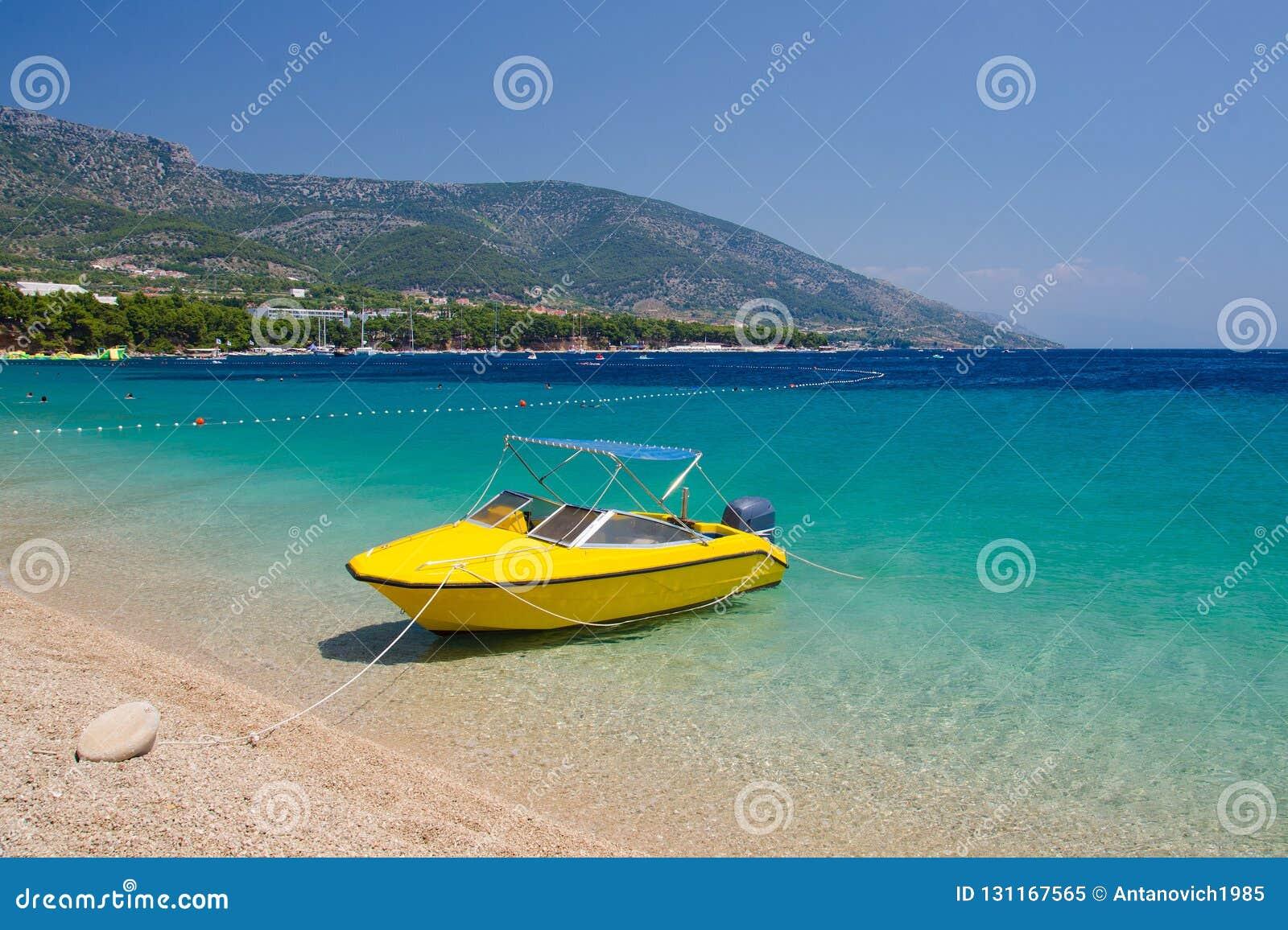 Barca gialla vicino al ratto di Zlatni del capo dell isola di Brac, mare adriatico, C