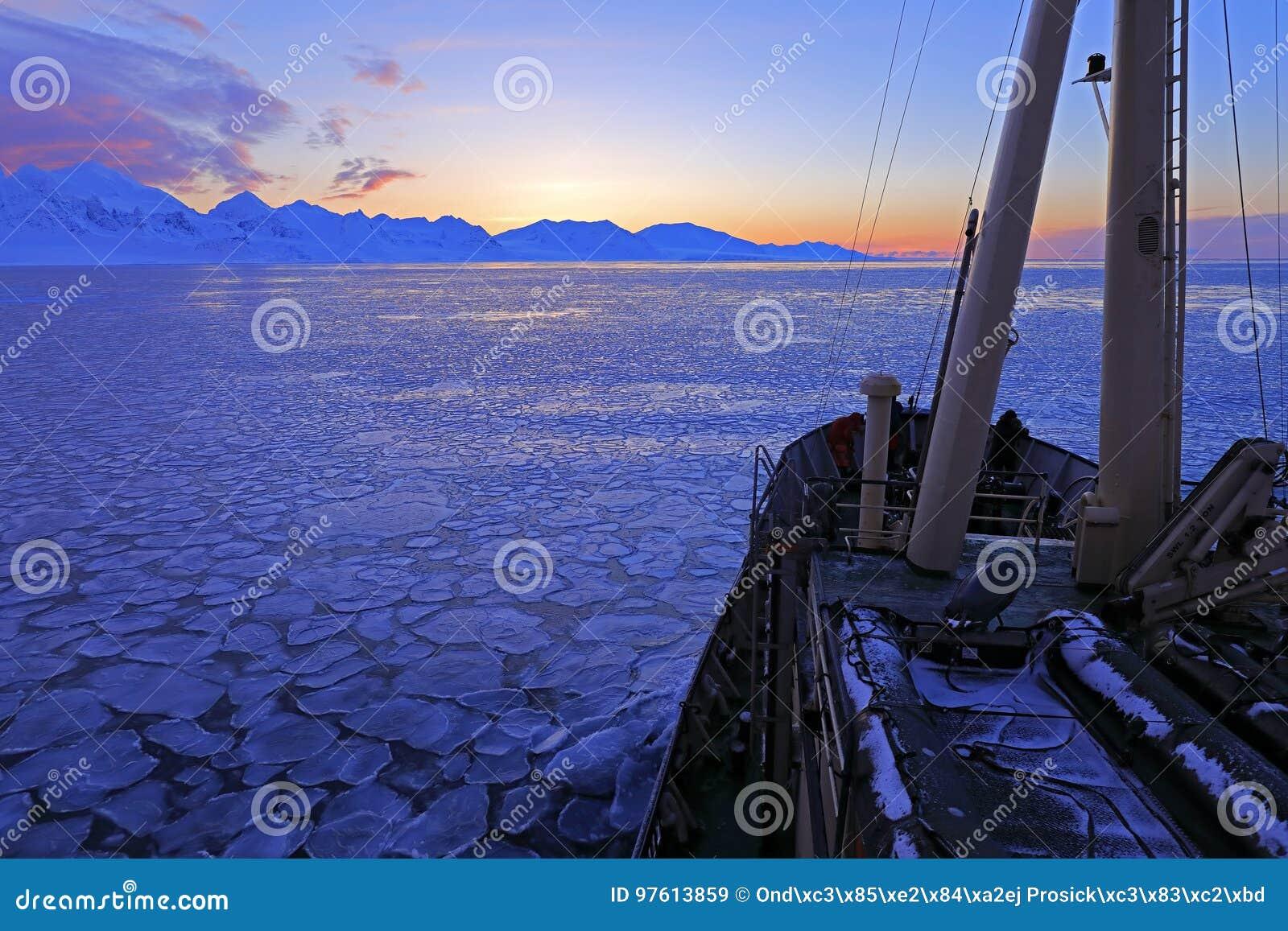 Barca nell Artide di inverno Montagna nevosa bianca, ghiacciaio blu le Svalbard, Norvegia Ghiaccio in oceano Penombra dell iceber