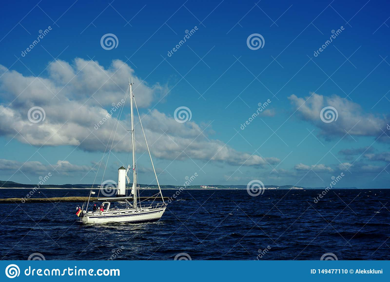 Barca a vela bianca in corso facendo uso del motore sulla terra del fondo