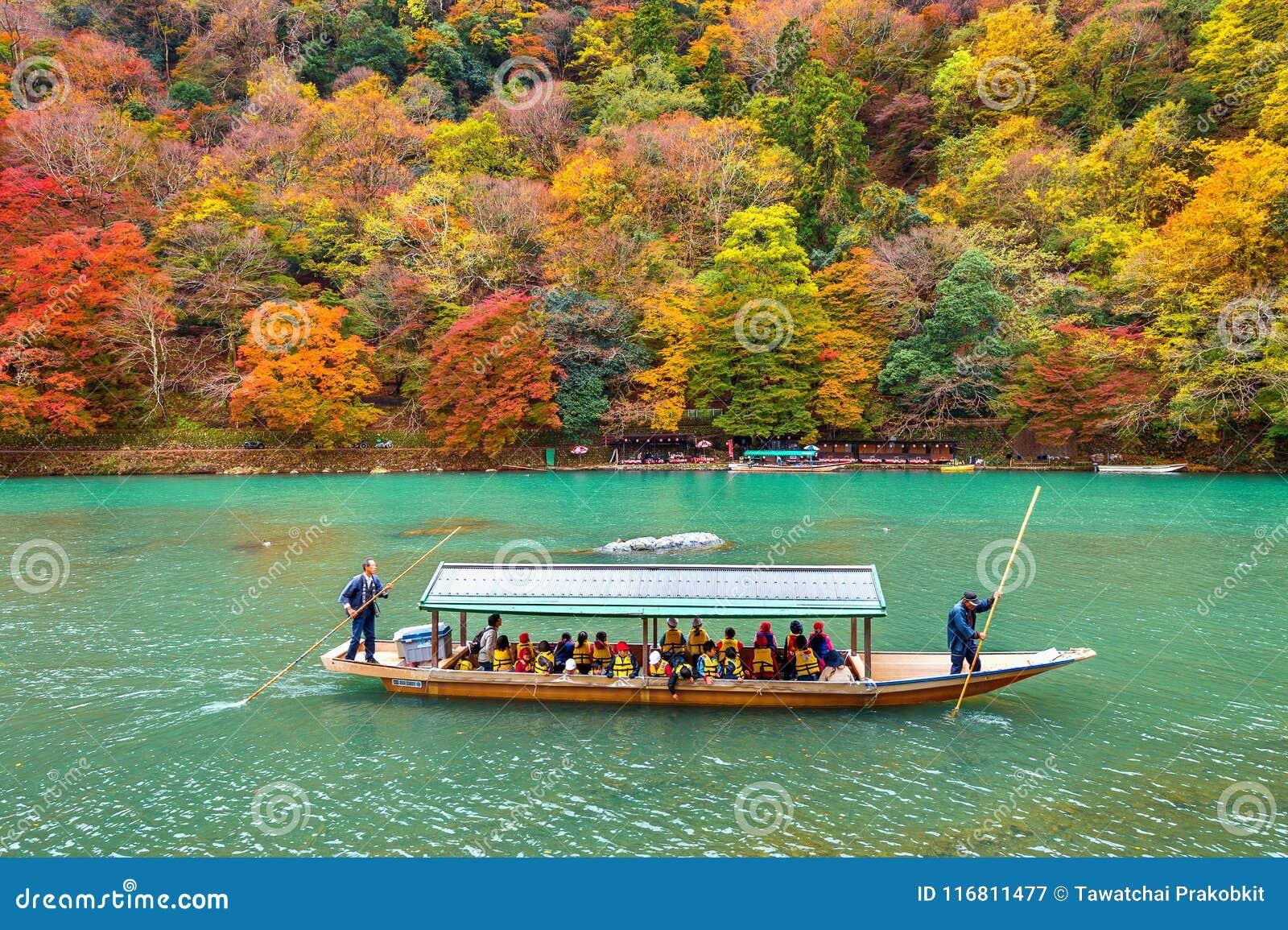 Barcaiolo che calcia la barca al fiume Arashiyama nella stagione di autunno lungo il fiume a Kyoto, Giappone
