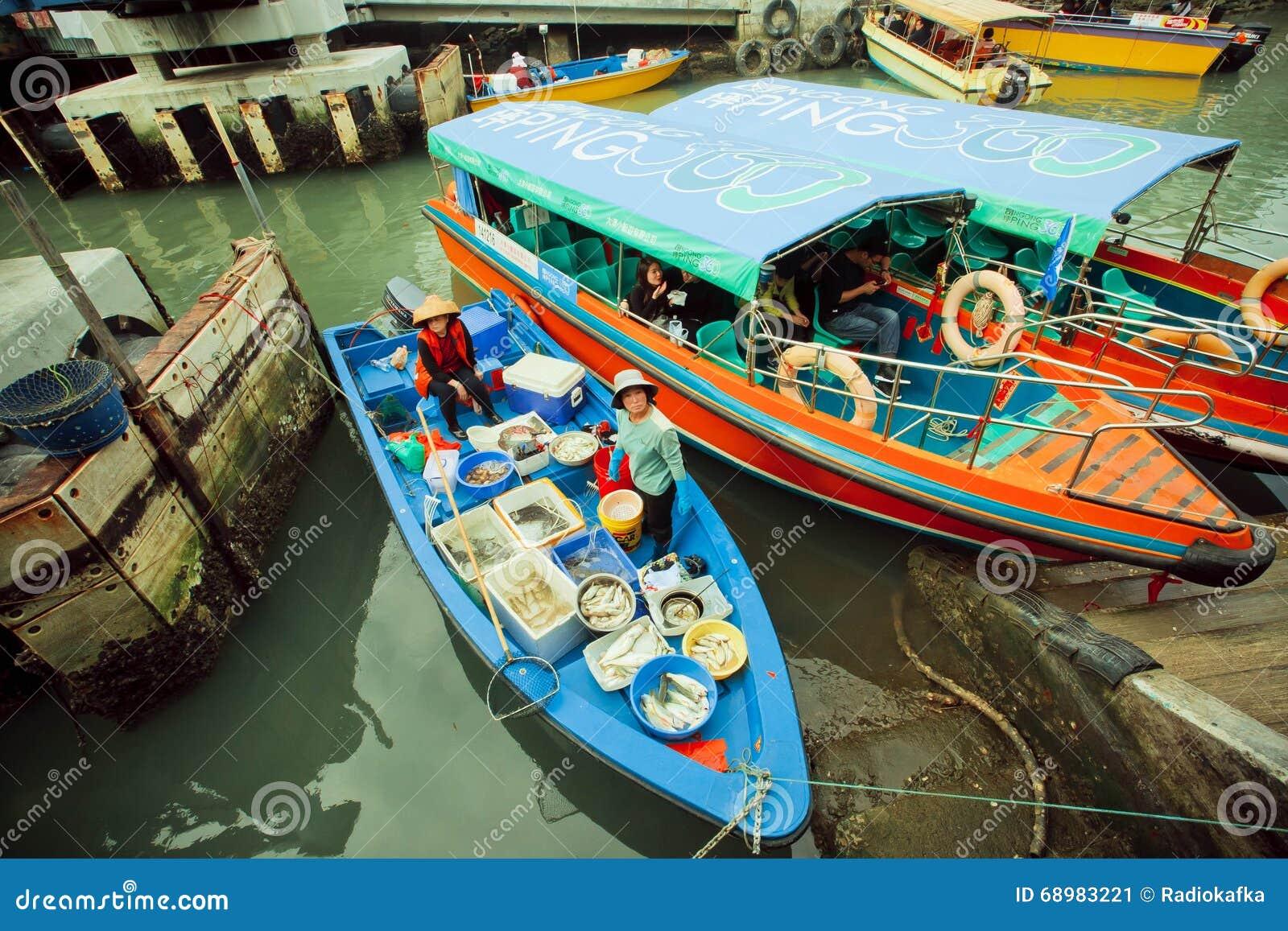 Barcas coloridas con los vendedores de los pescados y algunos turistas del pueblo pesquero