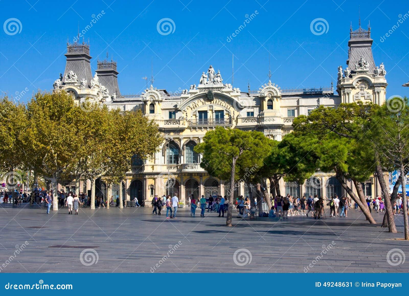 BARCELONA, ESPANHA - 18 DE OUTUBRO DE 2014: Os turistas aproximam a construção velha da autoridade portuária de Barcelona, porto