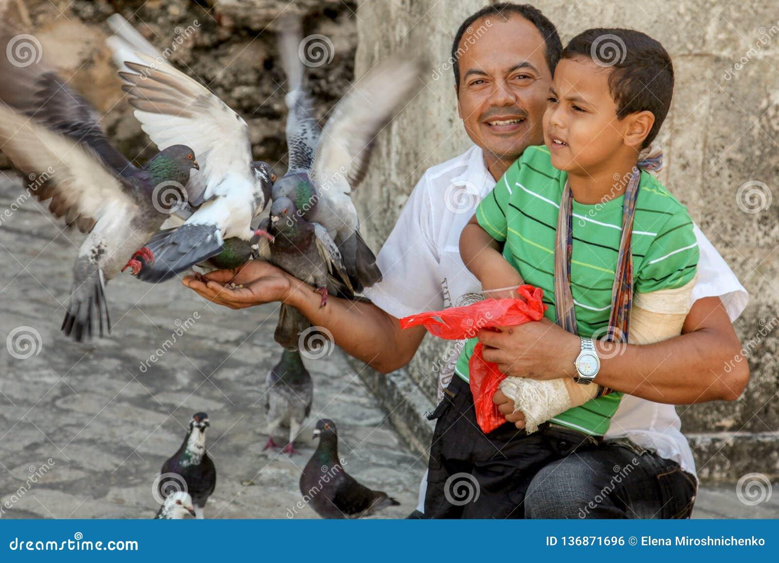 Barcelona, Hiszpania, Oct/- /2018: Dorosły łaciński mężczyzna z chłopiec na kolanach karmi gołębie na miasto ulicie Szczęśliwy ży