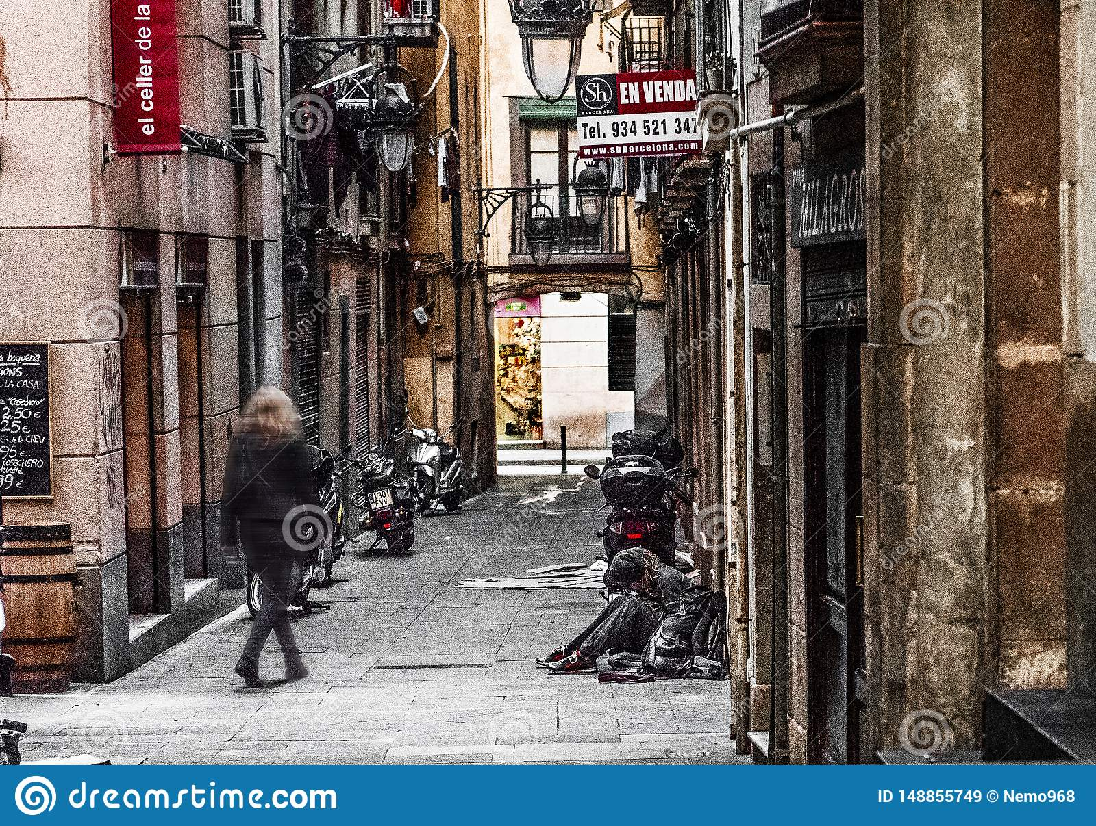 Barcelona Spain, downtown alley, narrow street, woman sitting on the ground