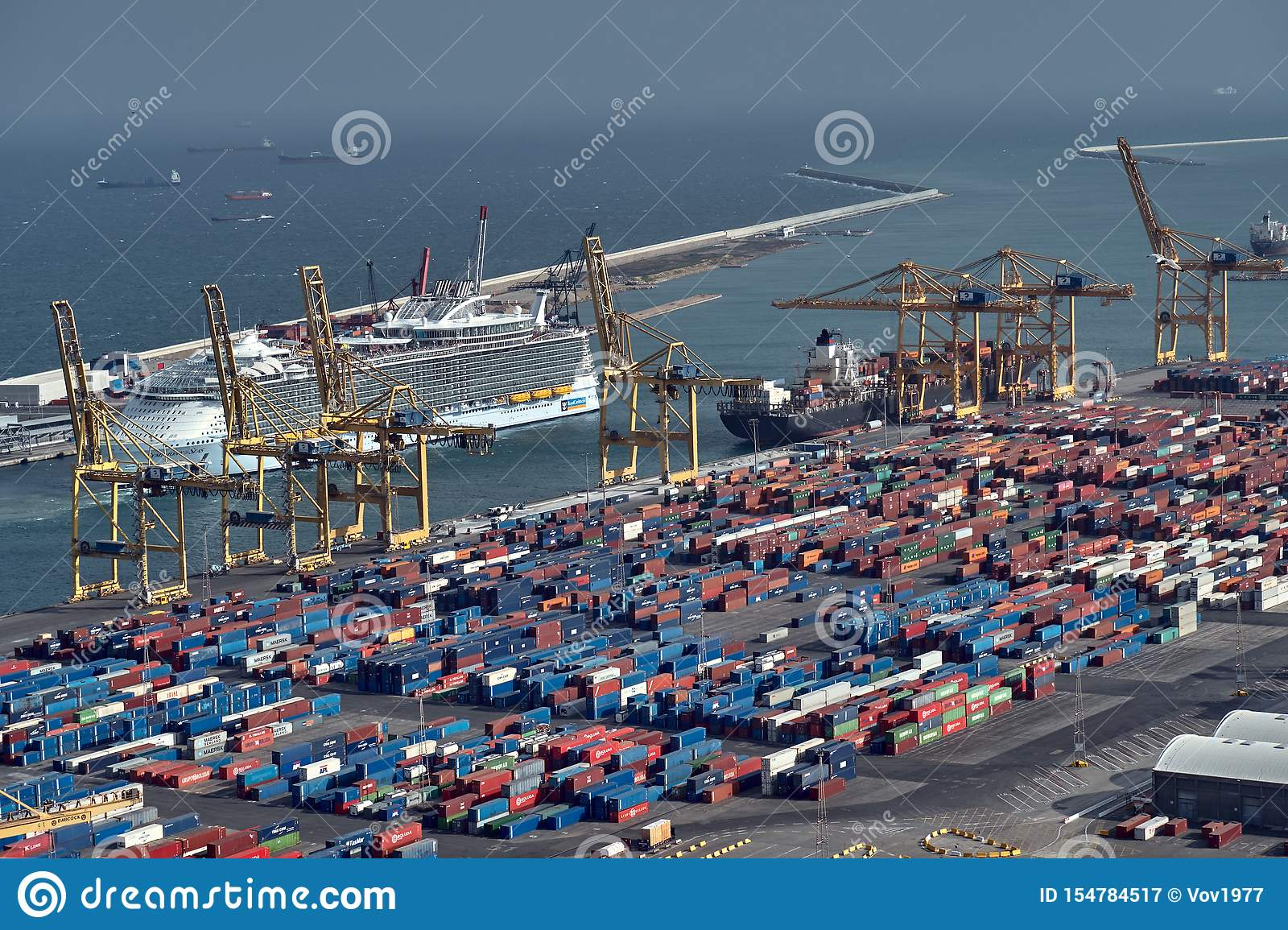 Barcelona, Spain - May, 27 2018: Blue and red metal cargo containers being loaded on cargo ship by huge port crane at the Sea Port