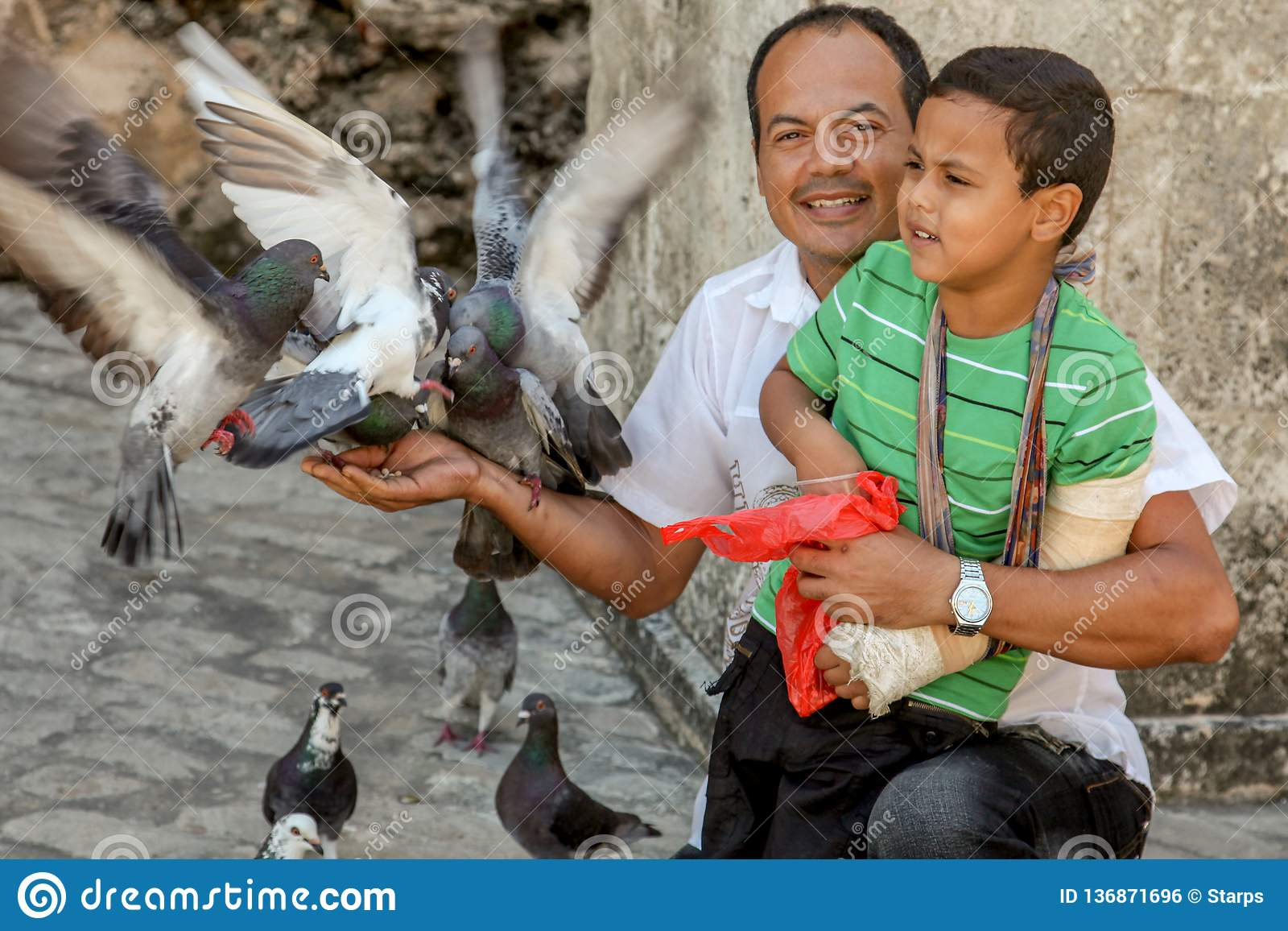 Barcelona / Spain - Oct./2018: Adult latin man with a boy on knees feeds the pigeons on the city street. Happy life, family values