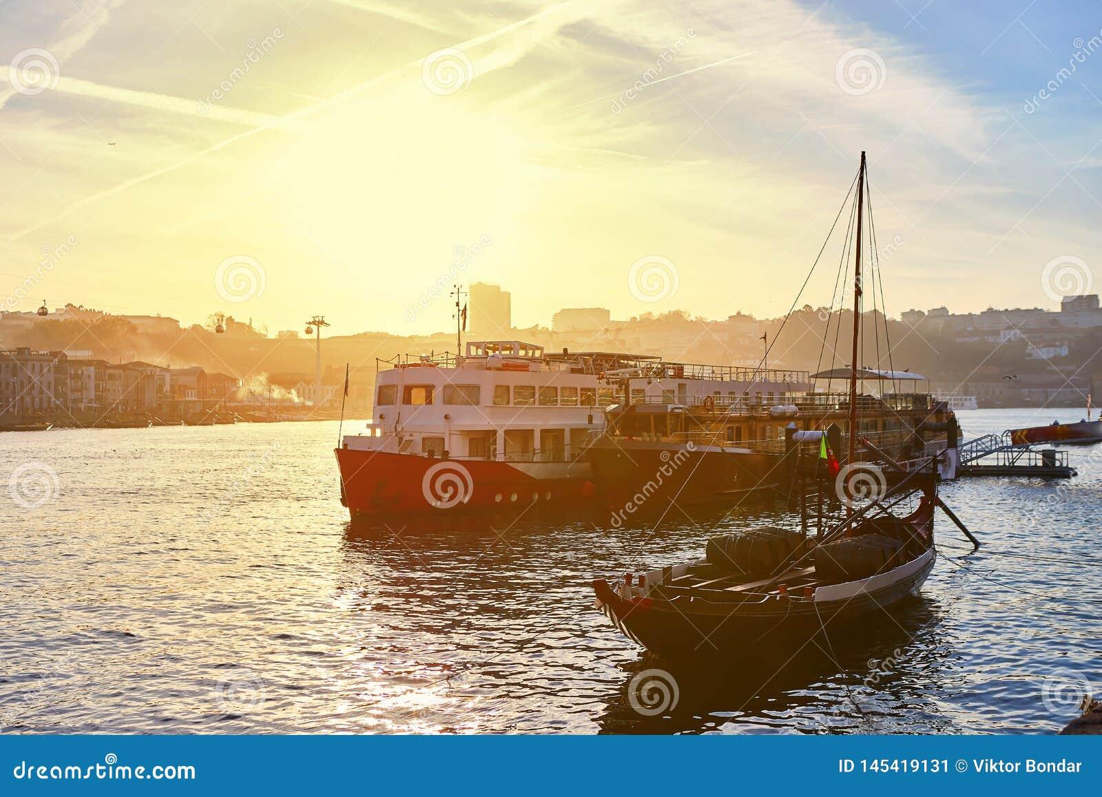"""Barche di legno portoghesi tipiche, chiamate """"rabelos di barcos """"che trasportano i barilotti di vino sul fiume il Duero con l"""