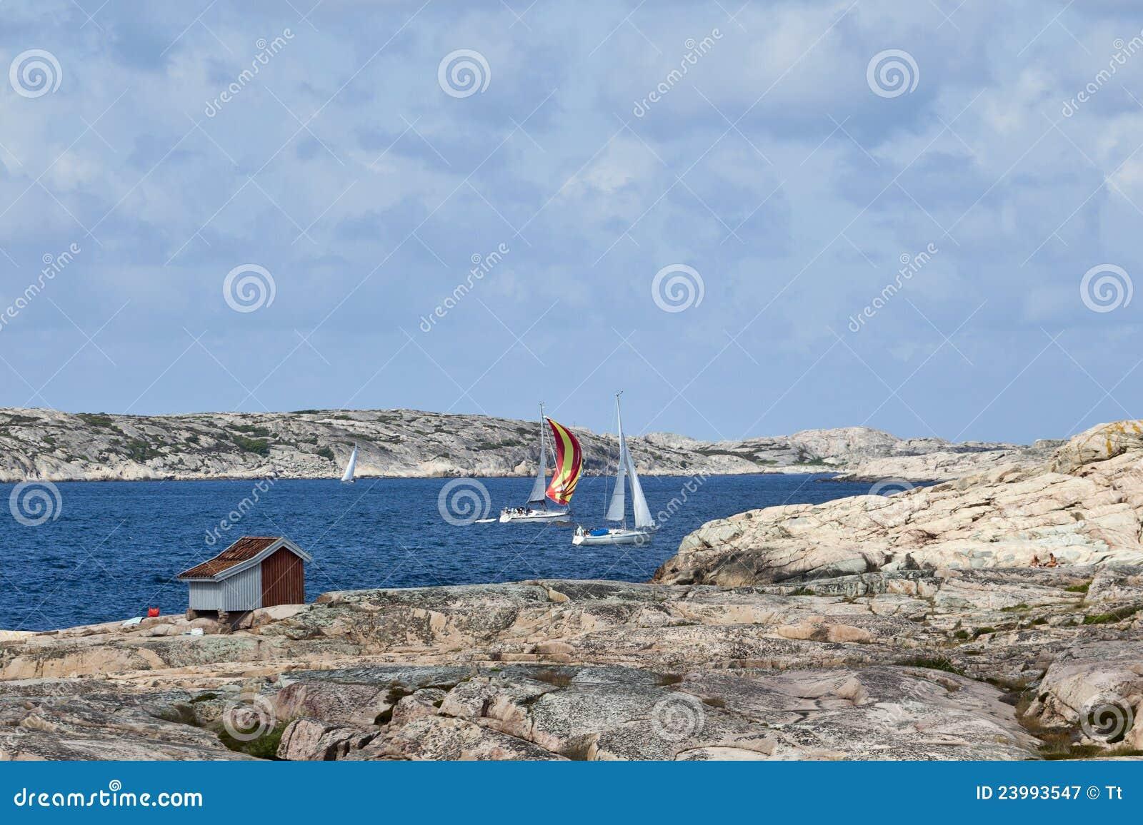 Barche a vela al litorale roccioso