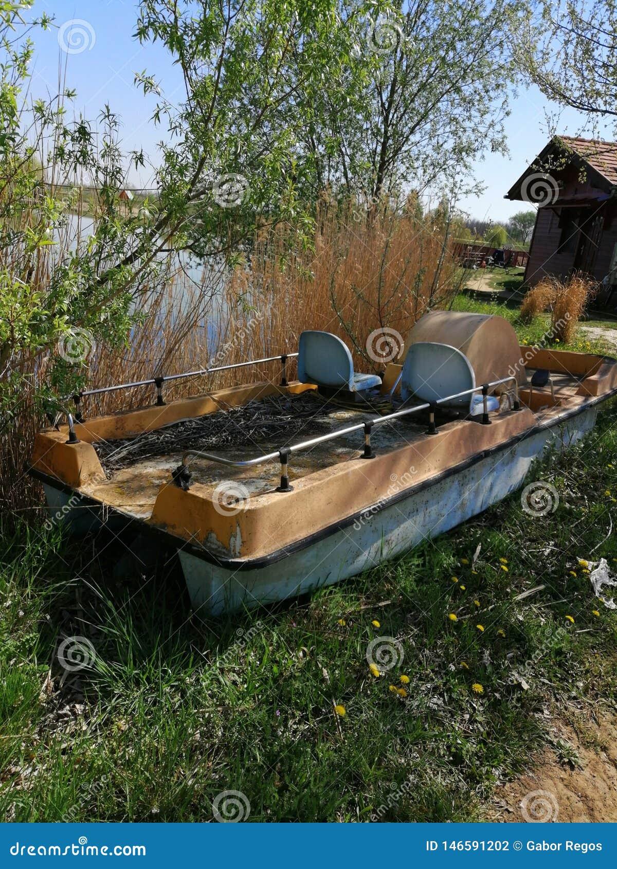 Barco abandonado ao lado de um lago