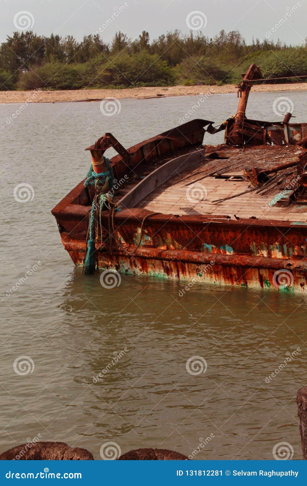 Barco abandonado do pescador em um porto pequeno indiano