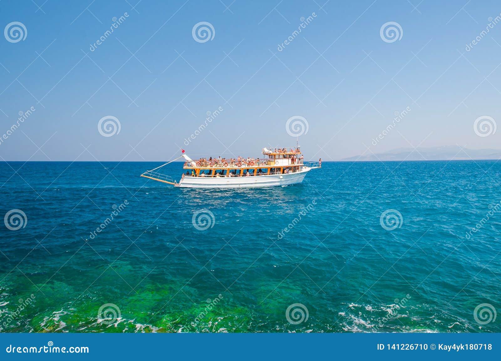Barco branco, navio, iate, navegando com os turistas ao longo da costa