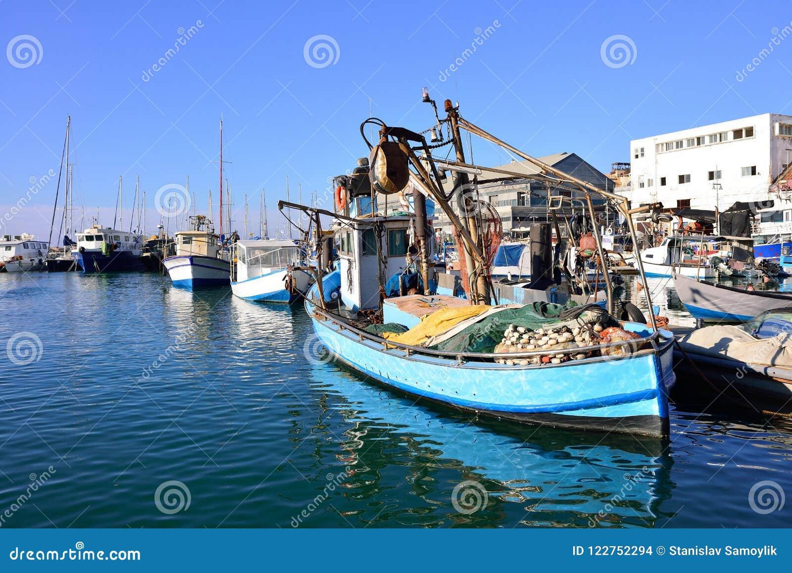 Barco colorido velho do pescador amarrado a um cais no porto de jaffa velho