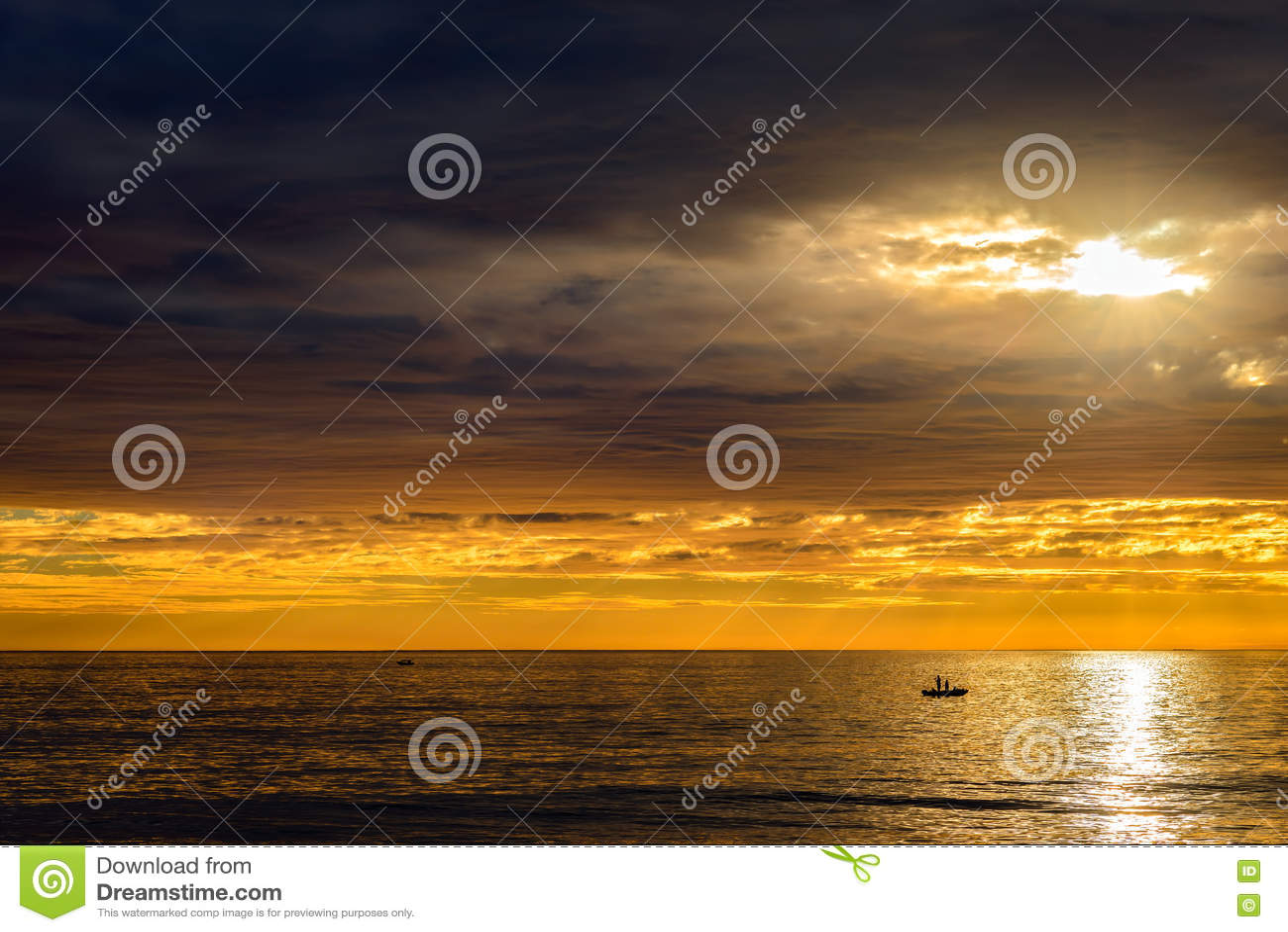 Barco com os pescadores no por do sol