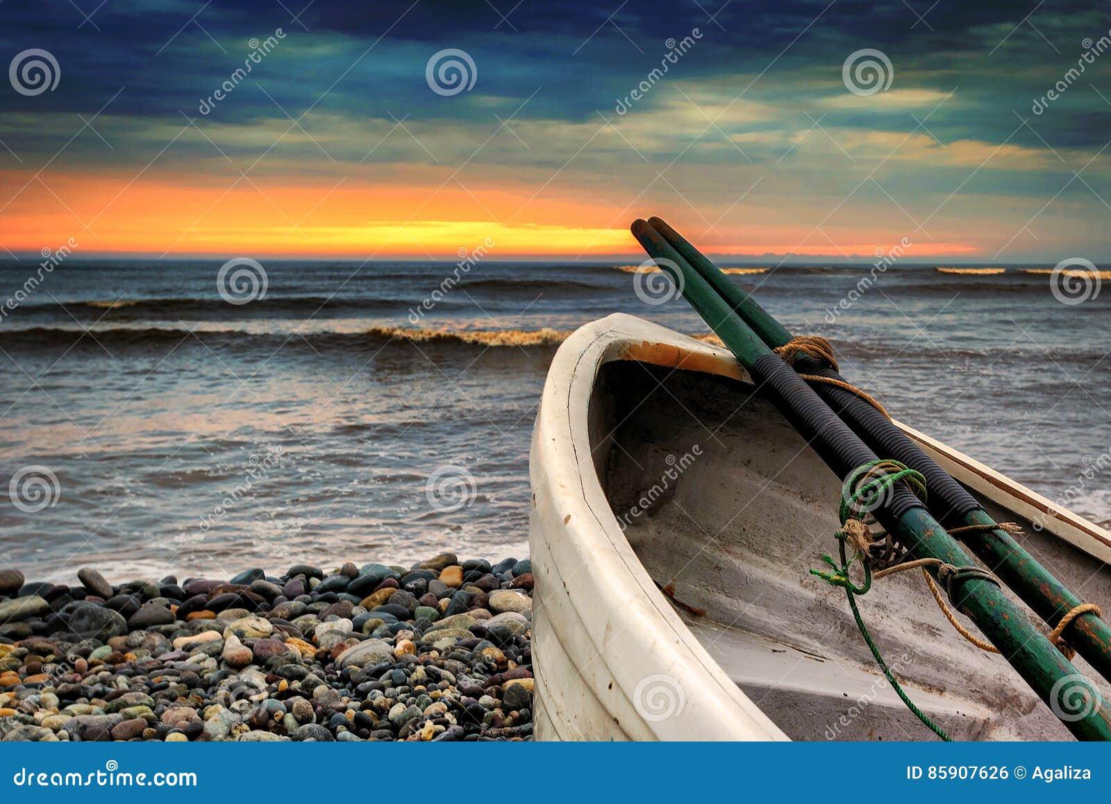Barco de fileira em Playa Waikiki em Lima, Peru no por do sol