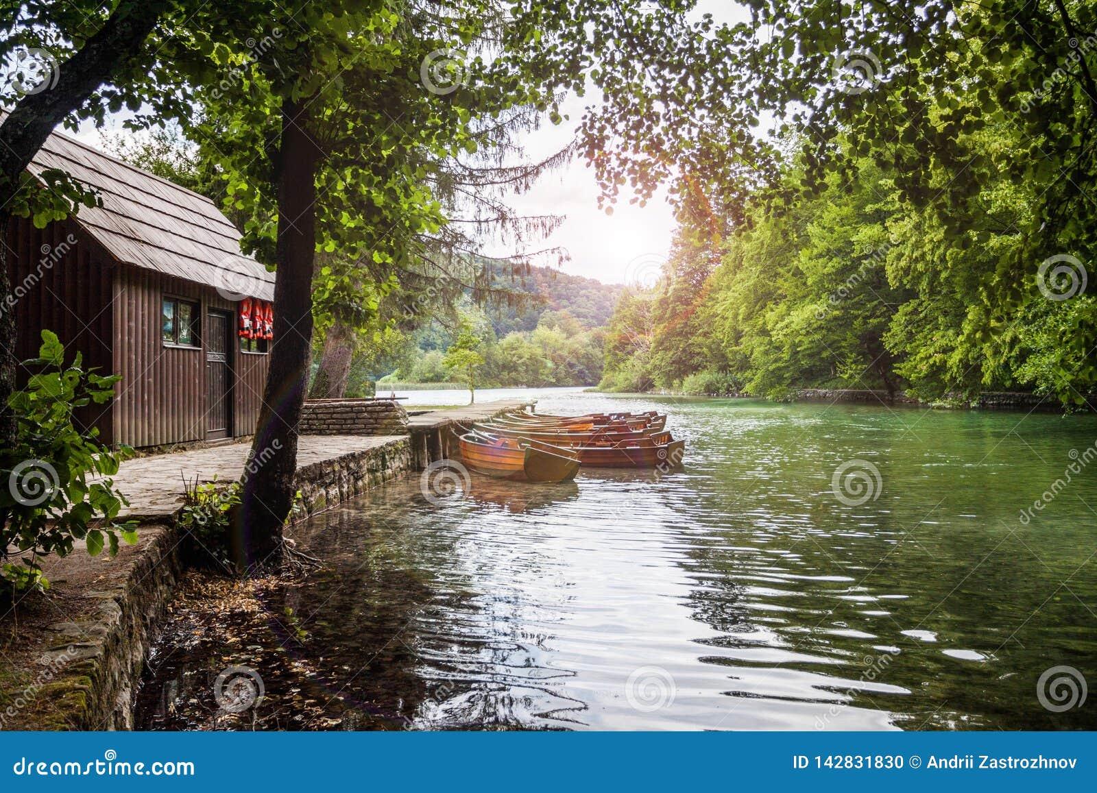 Barco de madera en el embarcadero en el lago claro hermoso en el bosque Plitvice, parque nacional, Croacia